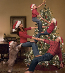 a family of four all standing on each other's knees for the youngest to put the star on the tree