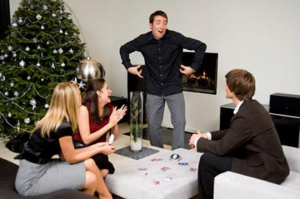 People playing charades in front of a Christmas tree