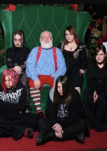 five kids in all black with dark hair and makeup sitting around Santa