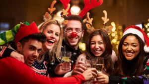 Family dressed in Christmas clothing raising their glasses