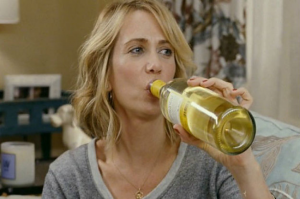 Kristen Wiig drinking white wine from the bottle