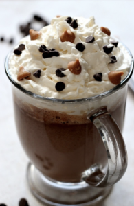 A mug of hot chocolate with whipped cream and peanut butter/chocolate chips