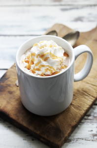 Hot chocolate topped with whipped cream and caramel sauce