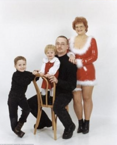 a classic family portrait post with mom dressed in a tight and short santa dress
