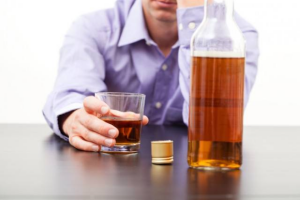 A stressed man gripping a glass of whiskey