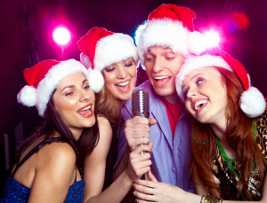 Friends wearing santa hats singing into a microphone