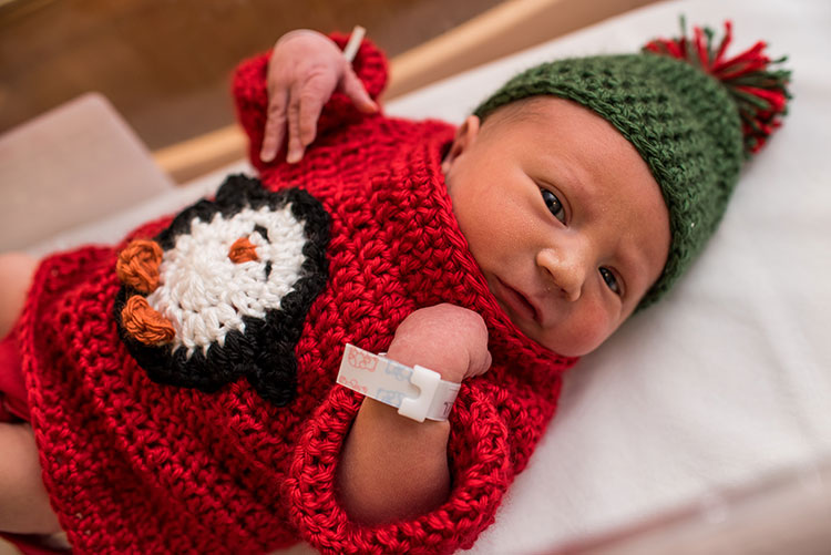 newborn baby in knit ugly christmas sweater