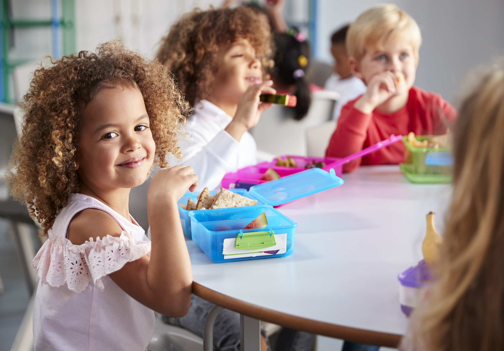 Close up of smiling young children sitting at a table eating their packed lunches together at infant school, girl smiling to camera, selective focus